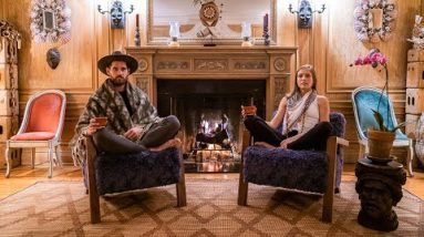 Yoga teacher couple sits in front of fire in complete silence
